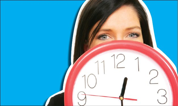 Teen in front of a blue background holding a red and white clock in front of her face