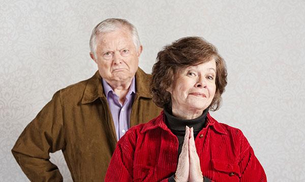Grumpy elderly man standing behind sneaky-looking elderly woman
