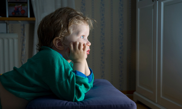 A young child in a green sweater glued to the TV screen