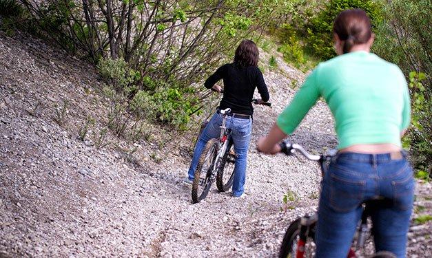Two girls on a rugged bike trail