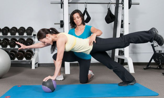 Woman in yoga pose working with a personal trainer