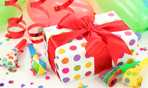 Wrapped presents, streamers and confetti on a white background