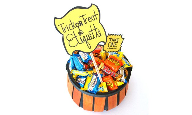 Bowl of candy with a sign that says trick or treat etiquette