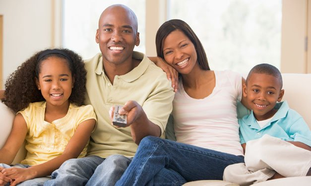 A family sitting on a couch as dad points the remote toward a tv out of shot
