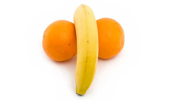 A banana sitting between two oranges